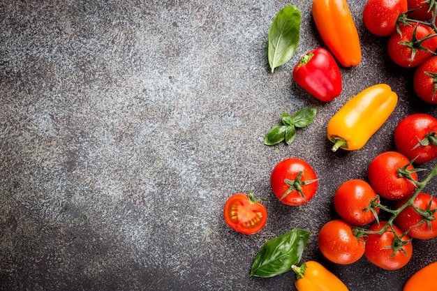 Fresh grape tomatoes with basil and pepper, top view with copy space