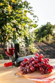 ブドウ園の木製テーブルにボトルと赤ワインのグラスと新鮮なブドウ