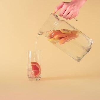 노란색 크림 파스텔 여름 배경의 주전자에 신선한 자몽과 레몬 주스 물. 현대 열대 추상 미술. 창조적 인 장식 최소한의 아이디어