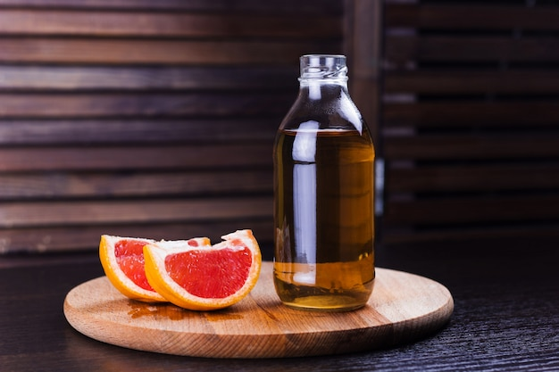 Fresh grapefruit  drink in a glass bottle wooden background