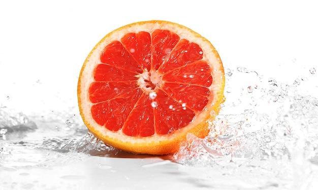 白で隔離の水しぶきの新鮮なグレープフルーツ