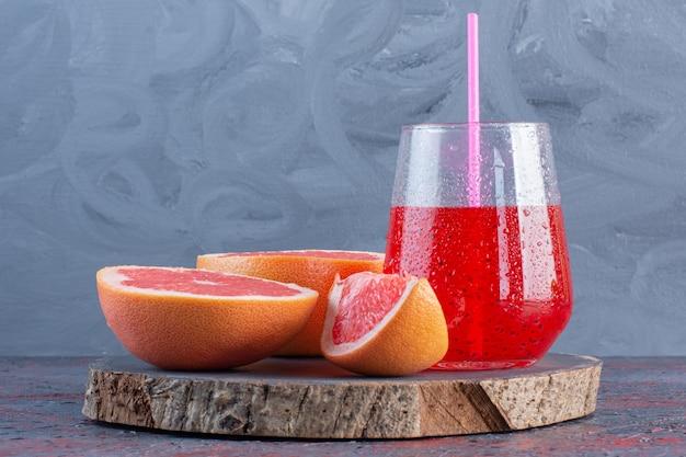 材料入りのフレッシュグレープフルーツジュース。木の板に