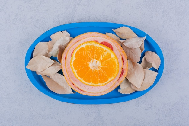 青いプレートに新鮮なグレープフルーツ、レモン、オレンジのリング。