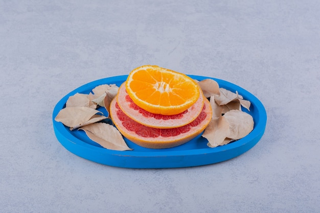 파란색 접시에 신선한 자몽, 레몬, 오렌지 링.