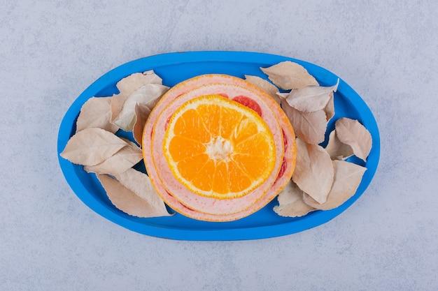 Anelli freschi di pompelmo, limone e arancia sulla zolla blu.
