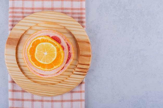 Fresh grapefruit, lemon and orange rings on wooden plate.