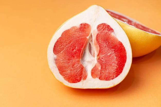 オレンジ色の表面に新鮮なグレープフルーツ、クローズアップ。セックスコンセプト。女性の健康の概念。