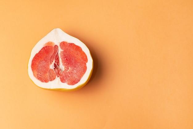 Fresh grapefruit on an orange surface