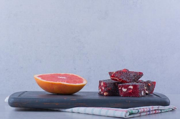 Кусочек свежего грейпфрута и вкусные восточные сладости на темной доске.