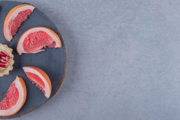 회색 나무 접시에 쿠키와 신선한 자 몽 슬라이스