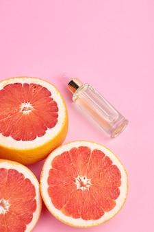 ピンクの背景にオイルガラス瓶と新鮮なグレープフルーツのスライス