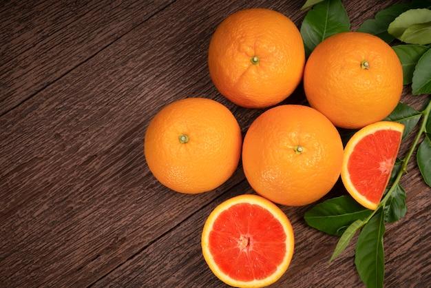 Свежий грейпфрут с ломтиками и листьями грейпфрута на деревянном фоне свежий грейпфрут на деревянном фоне