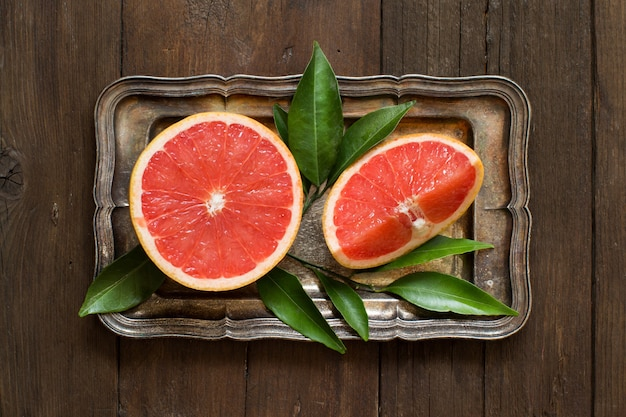 Fresh grapefruit with leaves  on a tray on a wooden table top view