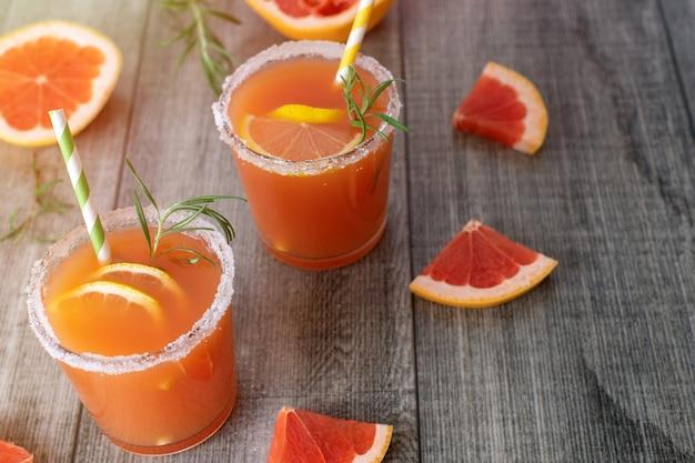 Свежие грейпфруты и два стакана грейпфрутового сока на сером деревянном столе.