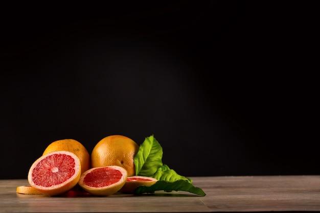 黒の背景に木製のテーブルの上の新鮮なグレープフルーツ