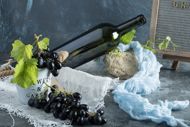 Fresh grapes in bucket with bottle of wine on sackcloth