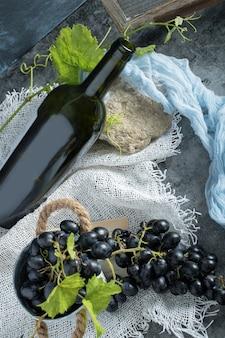 Uva fresca nel secchio con bottiglia di vino su tela di sacco
