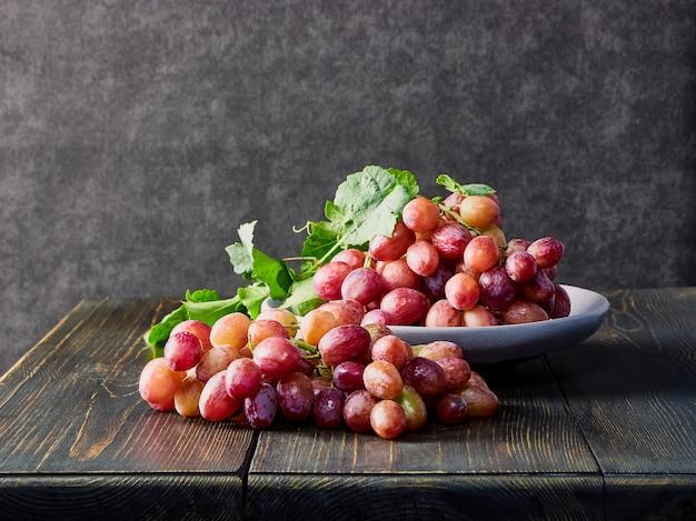 新鮮なブドウ。古い木製のテーブルの上のプレートにさまざまな品種の束