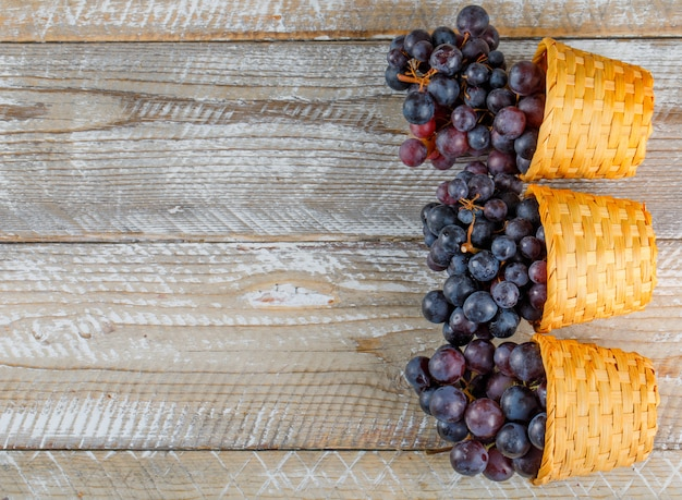 Fresh grapes in wicker baskets flat lay on a wooden background