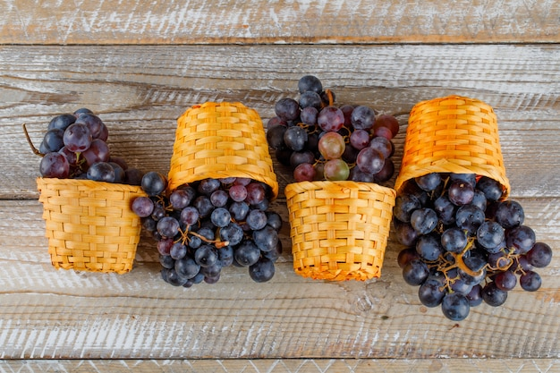 Fresh grapes in wicker baskets on a wooden background. flat lay.