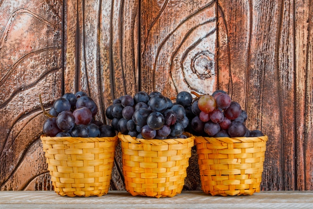 Fresh grapes in wicker baskets on wooden background, side view.