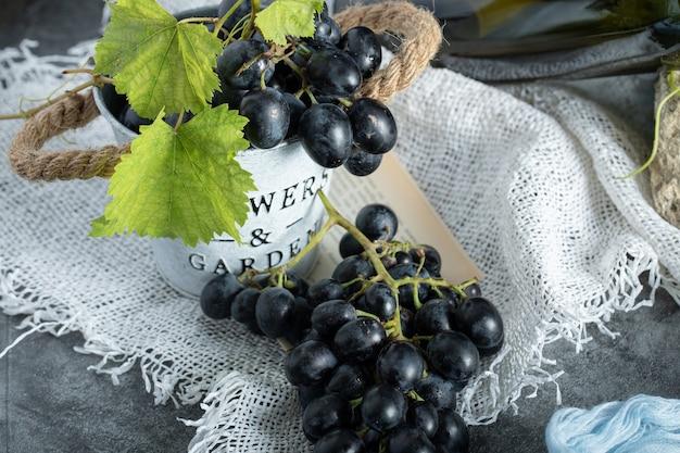 Uva fresca con foglie nel secchio su tela di sacco