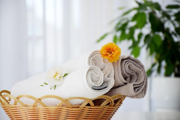 Свежие серые и белые полотенца, свернутые в плетеную корзину, украшенную цветами, и емкость для жидкости.