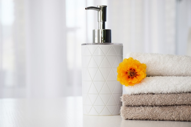 Fresh gray and white towels folded on white table, orange flower and liquid soap container