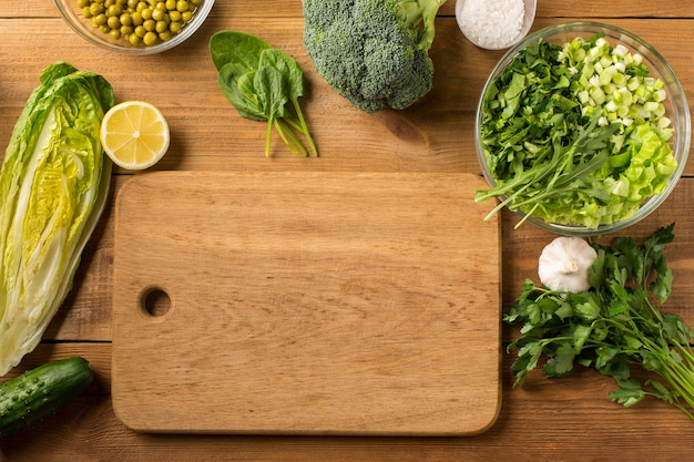 Fresh gree vegetables for salad on a wooden table with a cutting board. top view.