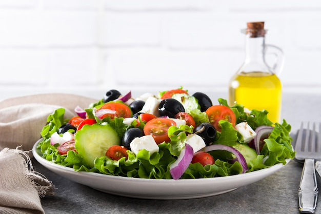 Fresh greek salad in bowl with black olive, tomato, feta cheese, cucumber and onion