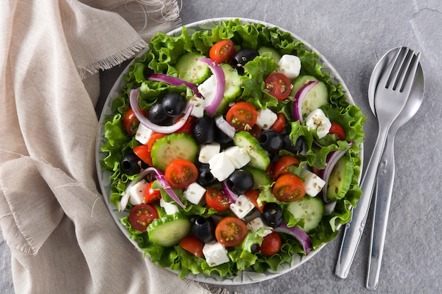 Fresh greek salad in plate with black olive,tomato,feta cheese, cucumber and onion on gray background top view