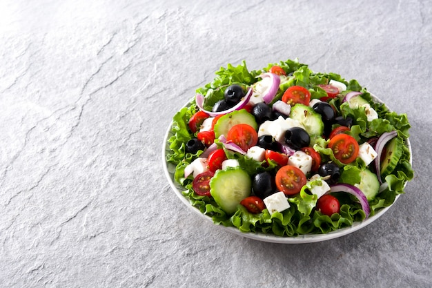Fresh greek salad in plate with black olive,tomato,feta cheese, cucumber and onion on gray copyspace
