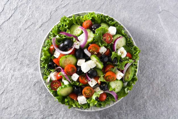 Fresh greek salad in plate with black olive,tomato,feta cheese, cucumber and onion on gray