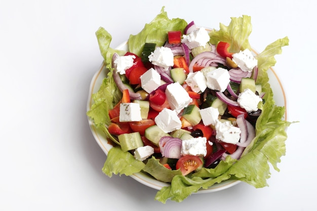Fresh greek salad in a salad bowl on a white background.