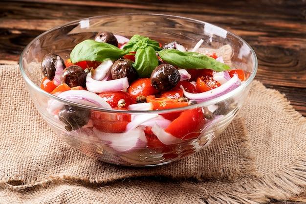 チェリートマト、オリーブ、タマネギ、スパイスを使った新鮮なギリシャ風サラダ。木製の背景のボウルにシーザーサラダ。健康的な有機ダイエット食品の概念