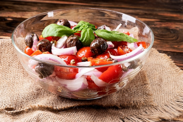 Fresh greek salad with cherry tomato, olives, onion and spices. caesar salad in a bowl on wooden background. healthy organic diet food concept