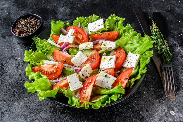 Fresh greek salad with vegetables and feta cheese in a plate. black table. top view.