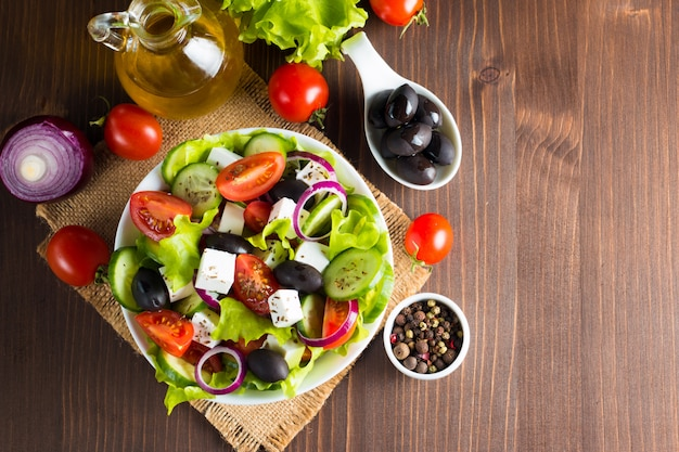 Fresh greek salad on wooden background.