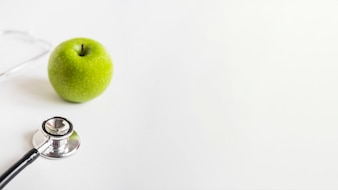 Fresh green apple and stethoscope isolated on white background