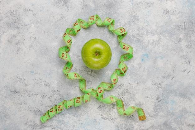 Свежее зеленое яблоко, рулетка и бутылка пресной воды на сером бетоне