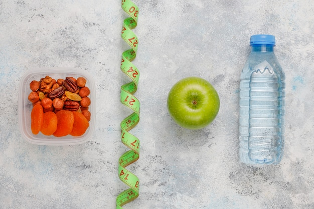 Fresh green apple, measure tape and bottle of fresh water on grey concrete