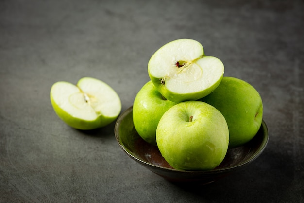 Fresh green apples cut in half put in black bowl on dark background