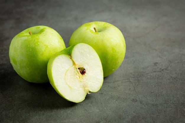 Разрезанные пополам свежие зеленые яблоки на темном фоне