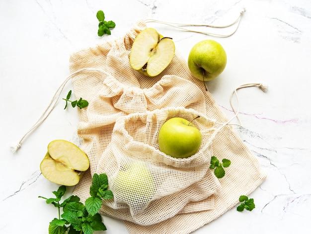 Свежие зеленые яблоки в сетчатых мешках