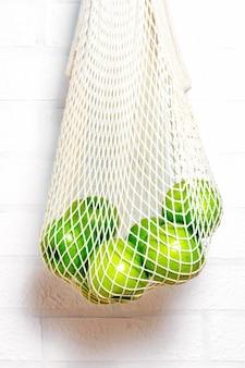 エコナチュラルの再利用可能なコットンメッシュバッグに入った新鮮な青リンゴ。