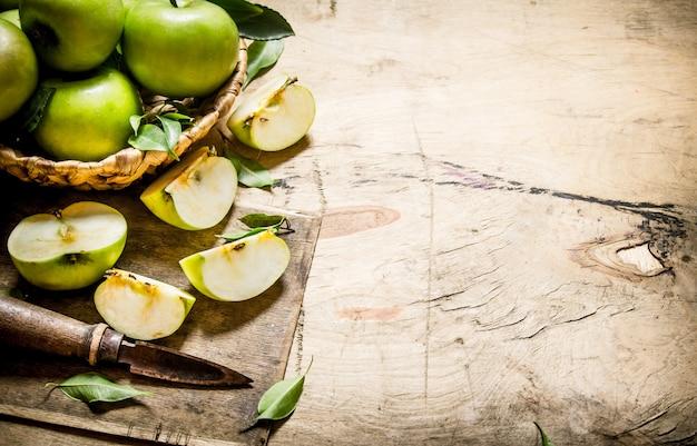 ナイフでバスケットに新鮮な青リンゴ