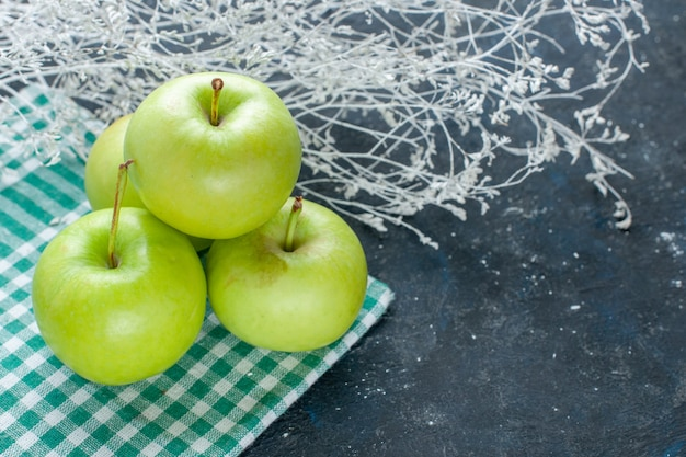 Mele verdi fresche dolci e succose acide su snack blu scuro, frutti di bosco, vitamina salute