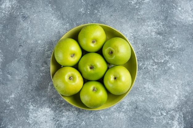 Свежие зеленые яблоки на зеленой тарелке