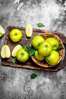 素朴なテーブルのまな板に新鮮な青リンゴ。