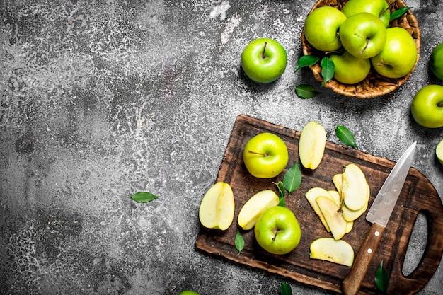 Свежие зеленые яблоки на разделочной доске на деревенском столе.
